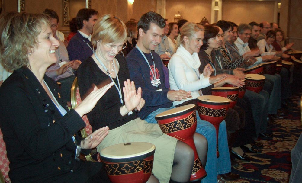 A room full of happy delegates playing drums - conference entertainment